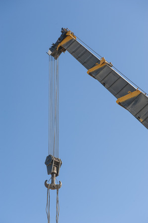jib: Large extended industrial crane jib boom arm against a blue sky background
