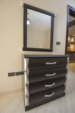 wall mirror: Set of drawers and wall mirror furniture in luxury apartment Stock Photo