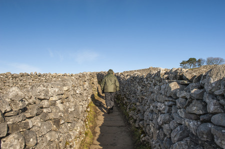 dry stone: People rambling walking on footpath between dry stone walls in the english countryside rural landscape Stock Photo