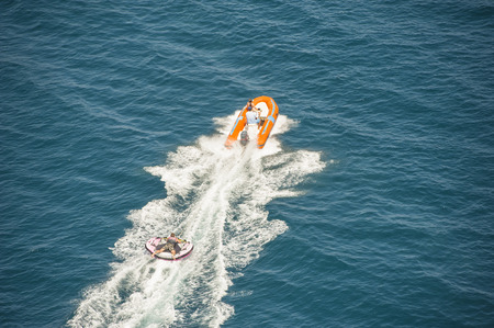 towed: Inflatable toy being towed behind a speed boat during summer tropical sea holiday vacation Stock Photo