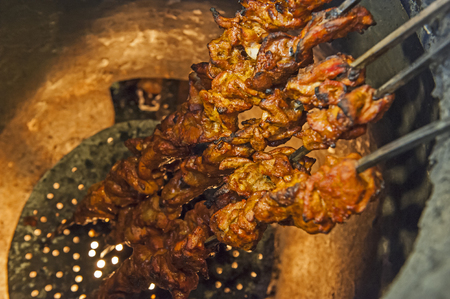 oven chicken: Closeup of chicken tikka kebabs cooking on skewers in indian tandoori oven Stock Photo