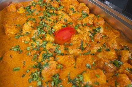 punjabi: Closeup detail of a dum aloo punjabi potato curry dish on display at an indian restaurant
