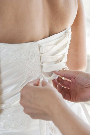 Closeup of the back of brides wedding dress corset being laced up