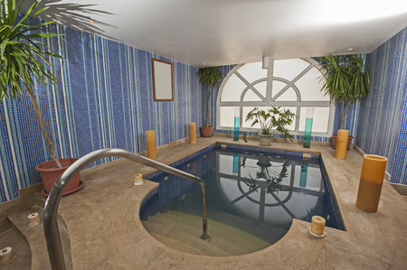 pool room: Large jacuzzi pool in room of luxury health spa center with candles
