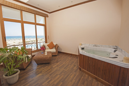 private club: Jacuzzi in private room of luxury health spa with chairs and sea view