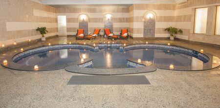 Grande piscina idromassaggio in camera del centro termale di lusso con le candele Archivio Fotografico