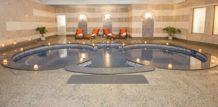 Large jacuzzi pool in room of luxury health spa center with candles