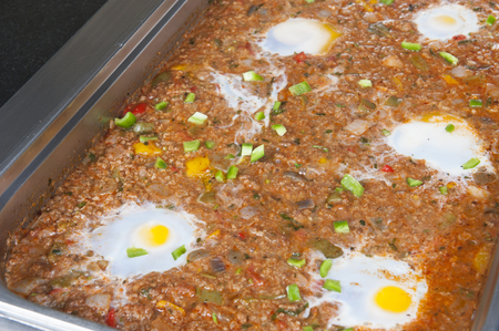 minced beef: Closeup detail of a minced beef with fried egg dish on display at an oriental restaurant buffet Stock Photo