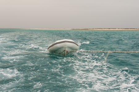 towed: Small inflatable motor boat being towed  on a tropical sea