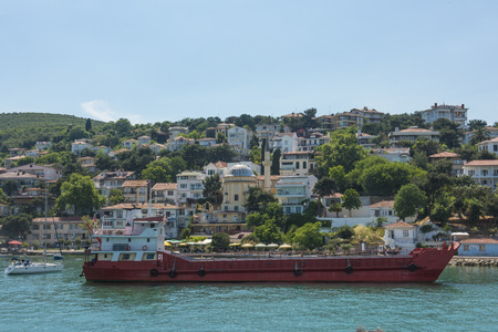residential housing: View of rural Princes Island of Kinaliada hillside with luxury residential housing and cargo ship on coast Stock Photo
