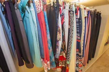 skirts: Variety of womens trousers and skirts clothing hanging on a rail in shop