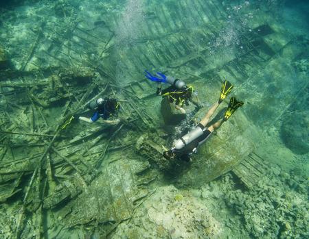 trio: Trio of scuba divers exploring the shipwreck of an underwater boat in the sea
