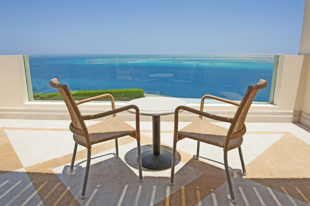 Tropical sea view from the balcony of a luxury resort with table and chairs Banco de Imagens