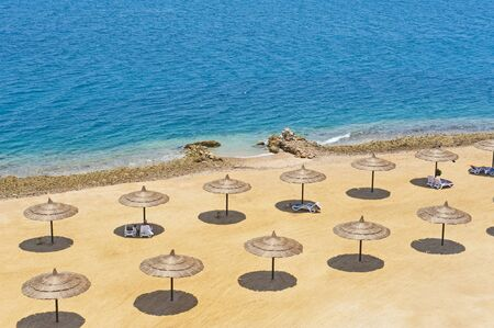parasols: Aerial view over a tropical beach with rows of parasols
