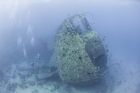 Scuba divers exploring the stern section of a large underwater shipwreck Stock Photo