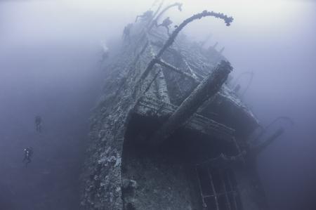 exploring: Technical scuba divers exploring a large deep underwater shipwreck Stock Photo
