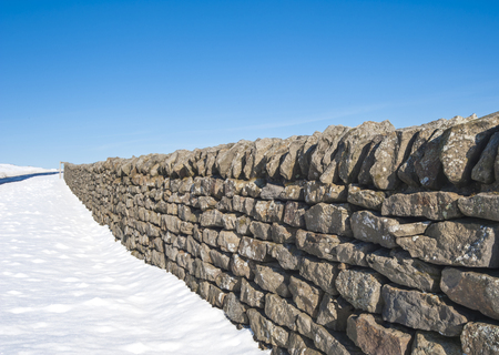 man made structure: Dry stone wall in an english snow covered winter countryside rural landscape