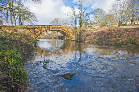 arched: Old arched stone bridge in english rural countryside setting over small stream Stock Photo