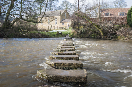 stepping: Stepping stones across a small river in english rural village countryside scene.