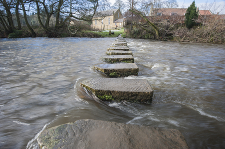 stepping stone: Stepping stones across a small river in english rural village countryside scene.