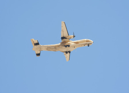 undercarriage: Large military tactical transport aircraft turboprop aeroplane in flight against blue sky background