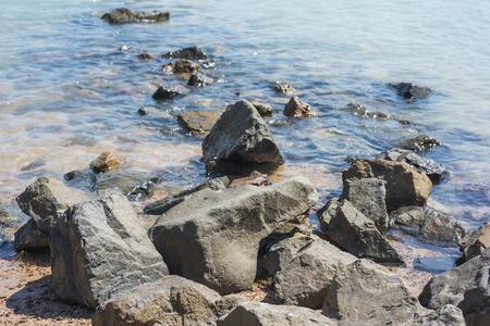 shore line: Closeup detail of rocks on a tropical beach shore line