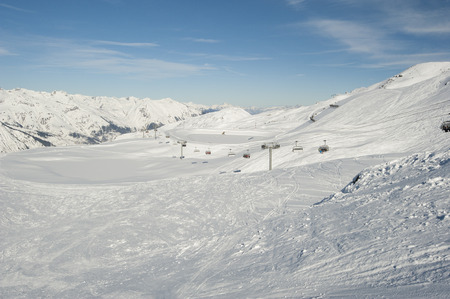 piste: View down a piste with skiers and chairlift on mountain