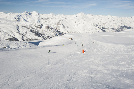 skiers: View down a piste with skiers and mountains Stock Photo