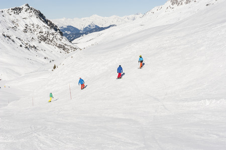 piste: View down a snowy alpine piste with snowboarders and mountains