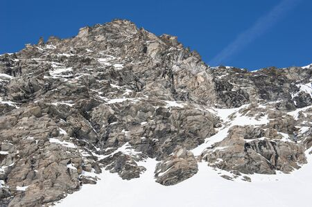 mountainside: Rugged alpine rocky mountainside covered in snow and ice Stock Photo