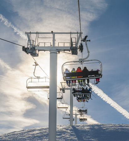 chairlift: Chairlift with skiers in the sun going over a snowy alpine mountain
