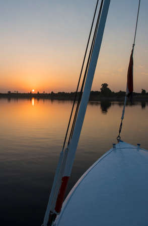 bow of boat: Sunset over a large river with bow of wooden sailing boat Stock Photo