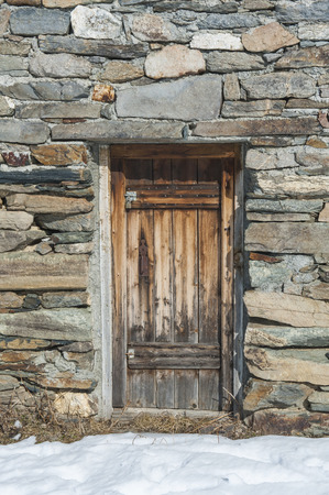 view of a wooden doorway: Wooden doorway of remote stone mountain hut on an alpine slope covered in snow Stock Photo