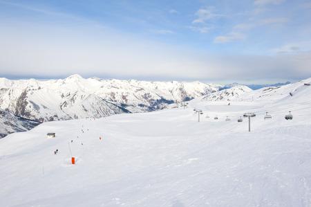 piste: View down a snowy ski piste in alpine mountain valley Stock Photo