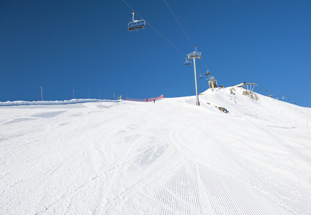 piste: View of a snowy ski piste in alpine mountain ski resort with chairlift