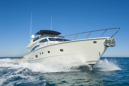 A luxury private motor yacht under way on tropical sea with bow wave Stock Photo