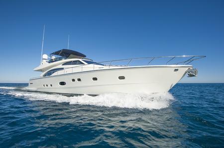 Een luxe privé-motorjacht aan de gang op tropische zee met boeggolf
