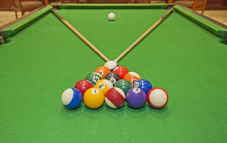 cues: Closeup detail of a pool billiards tables with balls and cues