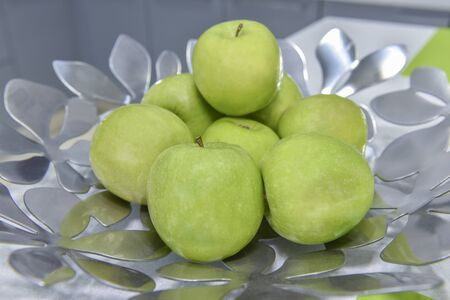 green apples: Collection of fresh green apples in a metal silver bowl on kitchen counter top Stock Photo