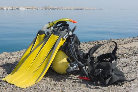 conjunto completo de equipo de buceo en el suelo junto a una costa de mar tropical