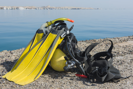 equipment: Full set of scuba diving equipment on the ground next to a tropical sea coast