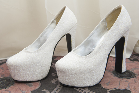high  heeled: Closeup detail of bridal high heeled platform stiletto wedding shoes on a sofa