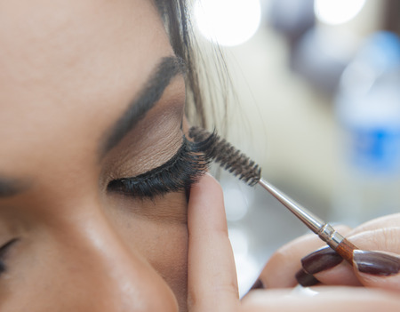 and eyelid: Closeup detail of womans eyelid and eyelash applying makeup mascara Stock Photo