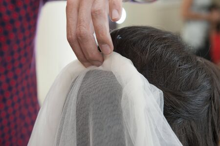 self image: Closeup detail of female bridal womens hair styling being styled at hairdresser salon with head piece veil