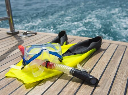 motor yacht: Snorkeling equipment on the wooden deck of a private luxury motor yacht traveling on tropical ocean