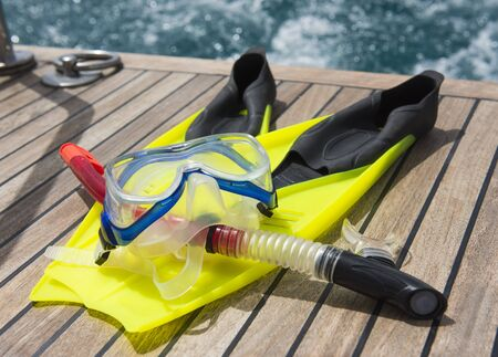 sail fin: Snorkeling equipment on the wooden deck of a private luxury motor yacht traveling on tropical ocean