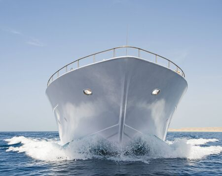 motor yacht: Bow of large luxury motor yacht sailing at sea on tropical ocean with wave Stock Photo