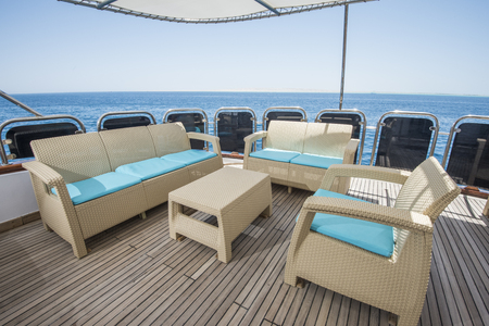 motor yacht: Rear teak deck of a large luxury motor yacht with chairs sofa table and tropical sea view background