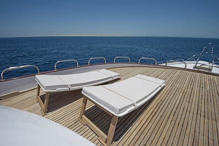 motor yacht: View over the bow of a large luxury motor yacht on tropical open ocean with sun loungers