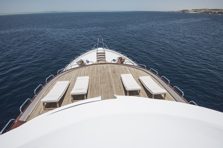 View over the bow of a large luxury motor yacht on tropical open ocean with sun loungers
